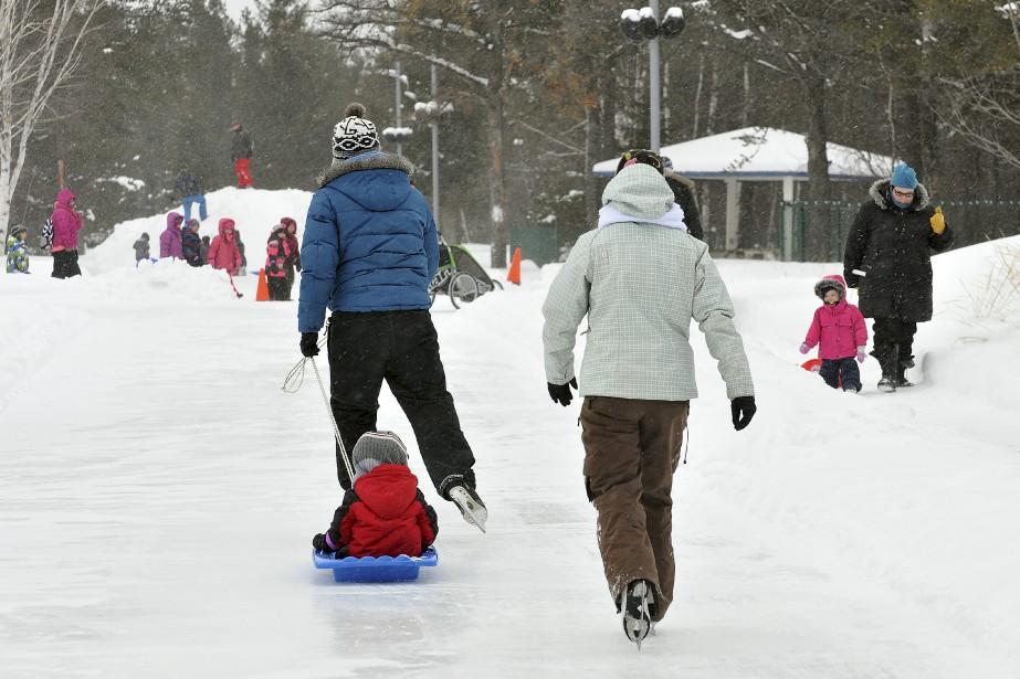 Les traîneaux deviennent plus commodes que les poussettes cette saison. Si le sentier glacé pour les patineurs a une belle longueur, d'autres visiteurs ont trouvé la glissade un peu petite. (Photo Le Progrès-Dimanche, Rocket Lavoie)