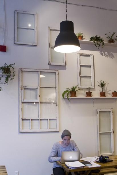 Les parents du propriétaire, André Philibert et Johanne Côté, ont trouvé et préparé les vieilles fenêtres qui décorent le mur. Son cousin, Étienne Bernier, étudiant en architecture, a créé l'arrangement. (Le Soleil, Caroline Grégoire)