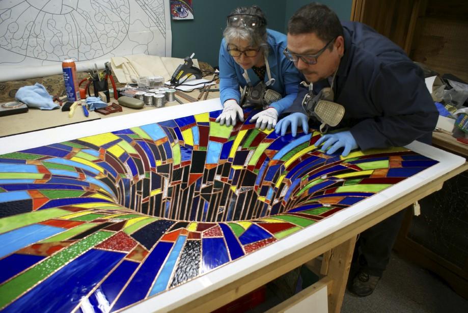Nancy Mackay et Paul Marois examinent leur vitrail baptisé <i>Lâcher prise</i> (2015), qui donne la saisissante illusion d'un cratère. (Nancy Mackay)