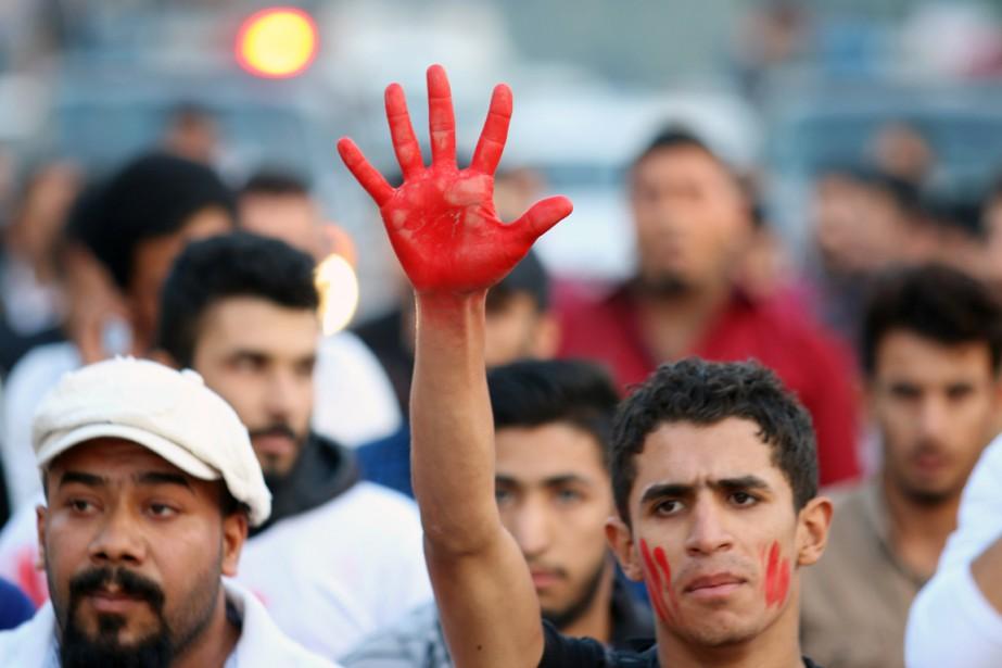Un activiste lève sa main peinte de rouge... (PHOTO HAIDAR MOHAMMED ALI, ARCHIVES AFP)