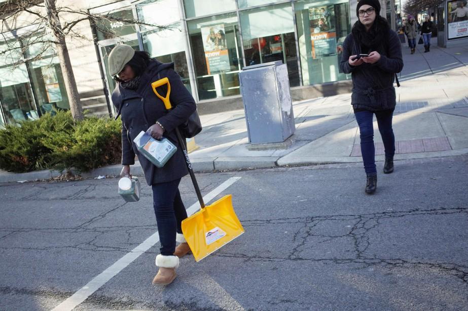Une résidante de Washington transporte une pelle et... (PHOTO MANDEL NGAN, AFP)