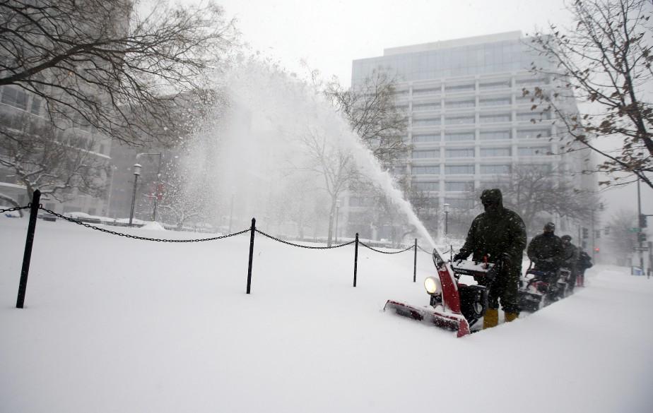 Des employés du service des parcs déneigent les trottoirs à Washington, qui prenait des allures de ville-fantôme samedi. (Associated Press)