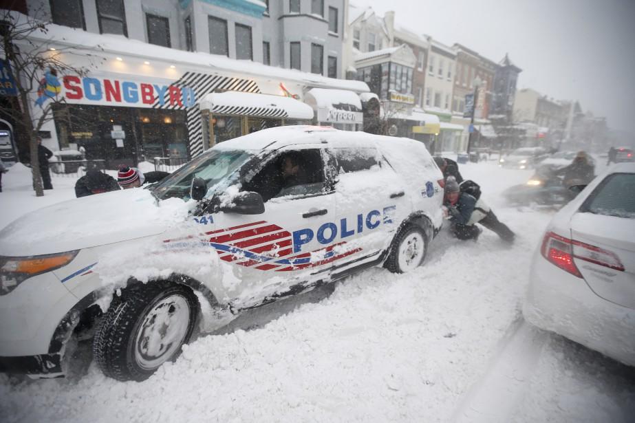 Des gens poussent une voiture de police coincée dans la neige à Washington. (Associated Press)