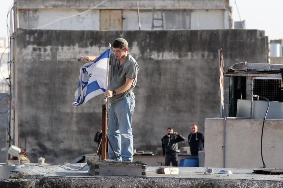 Un colon israélien installe un drapeau de l'État... (PHOTO HAZEM BADER, ARCHIVES AFP)