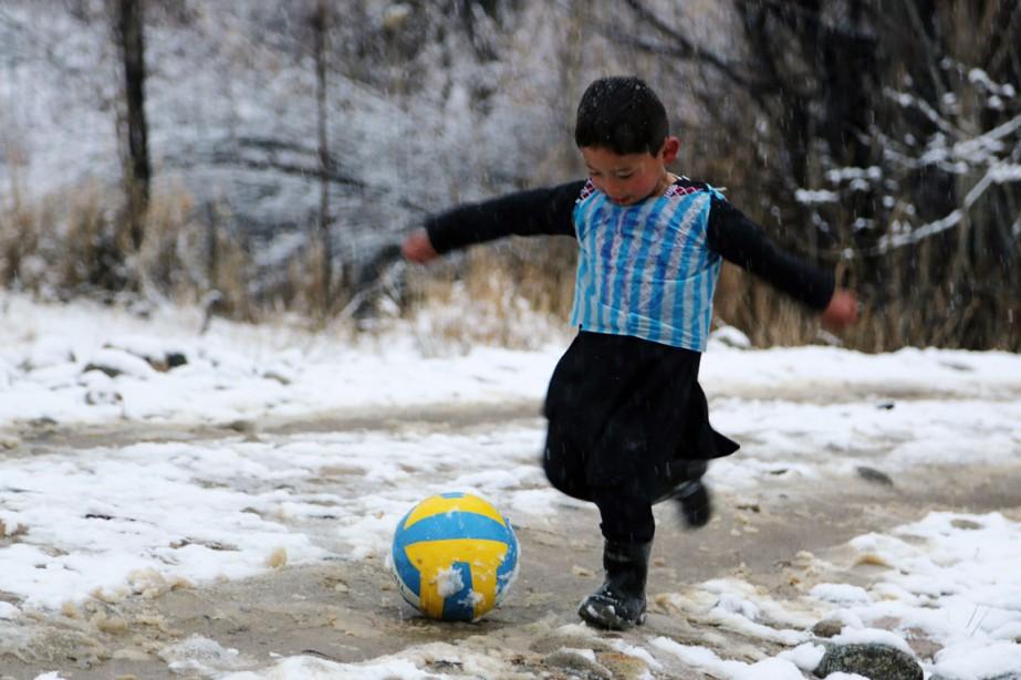 Ce garçonnet en bottes caoutchouc et shalwar kameez... (PHOTO AFP/STR)