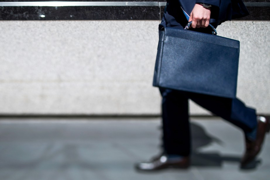 A man carrying a briefcase walks past the...