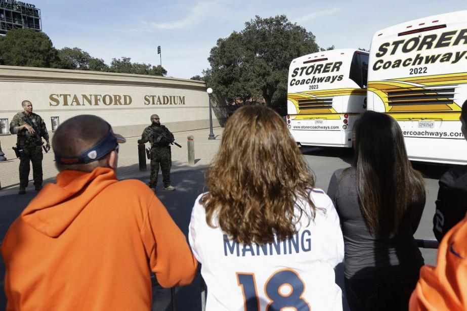 Des officiers surveillent les autobus des partisans des... (PHOTO JEFF CHIU, AP)