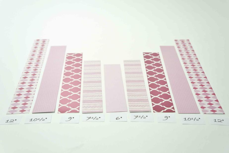 Étape 2.Tailler les bandes sur la longueur pour en obtenir deux de 30,4cm (12po), deux bandes de 26,6cm (10,5po), deux bandes de 23cm (9po), deux bandes de 19cm (7,5po) et une bande de 15,2cm (6po) pour le centre (papier uni ou motifs recto verso). Étape 3.Superposer les bandes, en mettant la plus courte au centre (6 pouces) et en ajoutant de part et d'autre en ordre croissant celles de 7,5 pouces, 9 pouces, 10,5 pouces et 12 pouces. Toutes les bandes doivent être alignées au bas. (Fournie par Michaels)