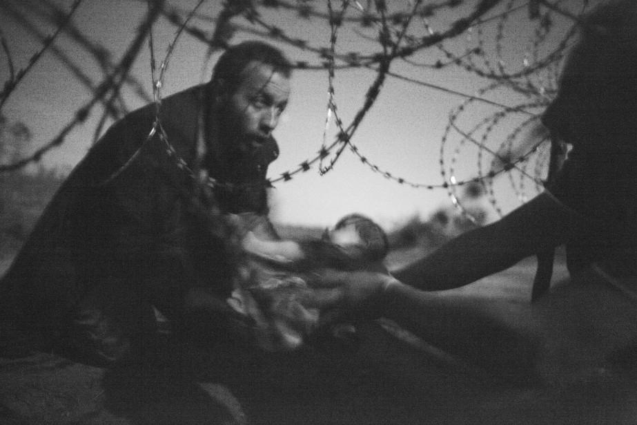 Grand Prix du World Press Photo: «Rêve d'une vie meilleure», du photographe indépendant australien Warren Richardson. Prise le 28 août 2015 à Roszke, Hongrie, elle montre un réfugié portant un enfant qui tente de traverser des barbelés à la frontière serbe. (Fournie par World Press Photo)