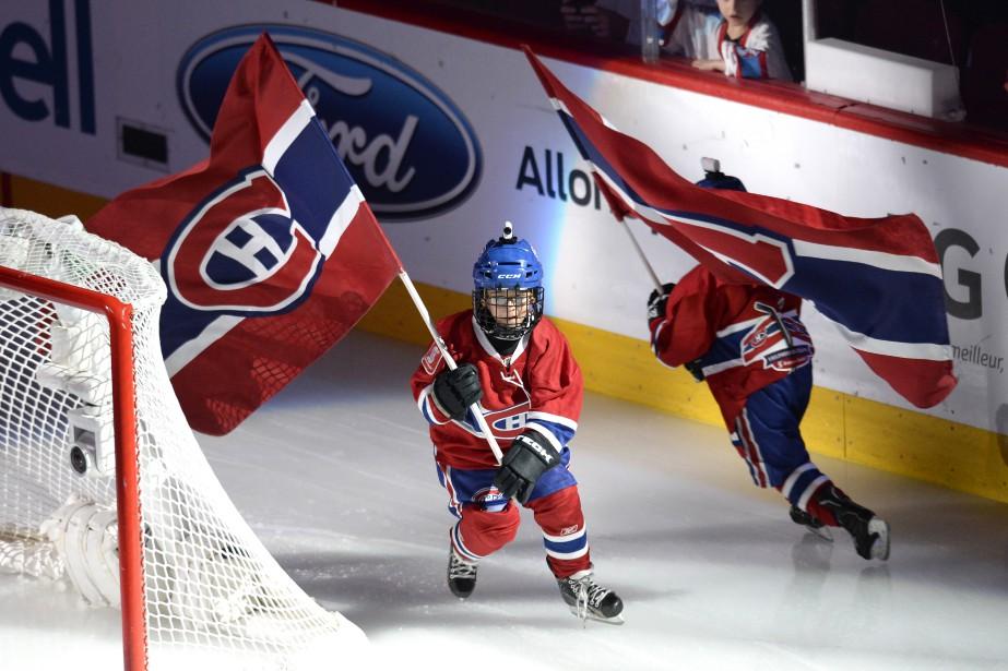 Deux jeunes partisans portent des drapeaux aux couleurs du Canadien lors des cérémonies d'avant-match. (PHOTO BERNARD BRAULT, LA PRESSE)