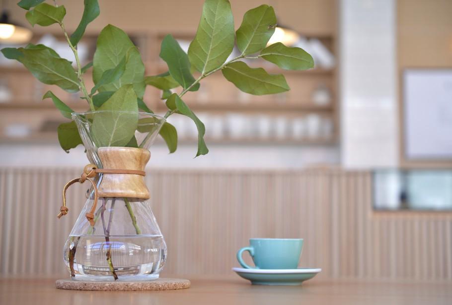 Sur les tables réfectoire, des cafetières Chemex en verre ceinturées de bois et lacées de cuir sont transformés en vases et accueillent quelques branches. Vendues sur place 50 $. (Le Soleil, Yan Doublet)