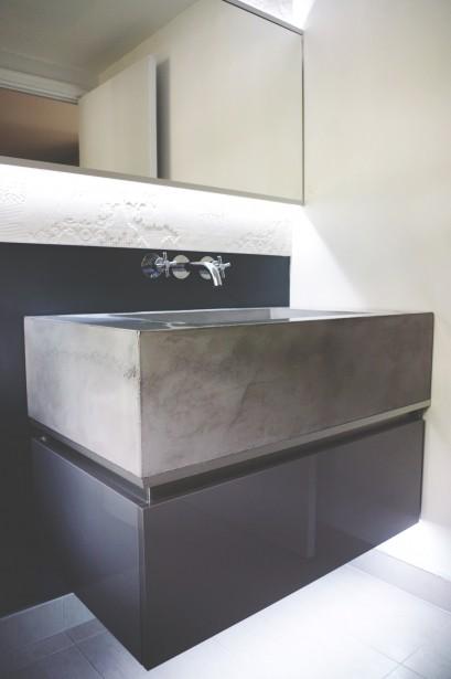 Des rubans de DEL ont été fixés sous un meuble-lavabo flottant et derrière le miroir pour mettre en évidence le relief de la céramique. ()