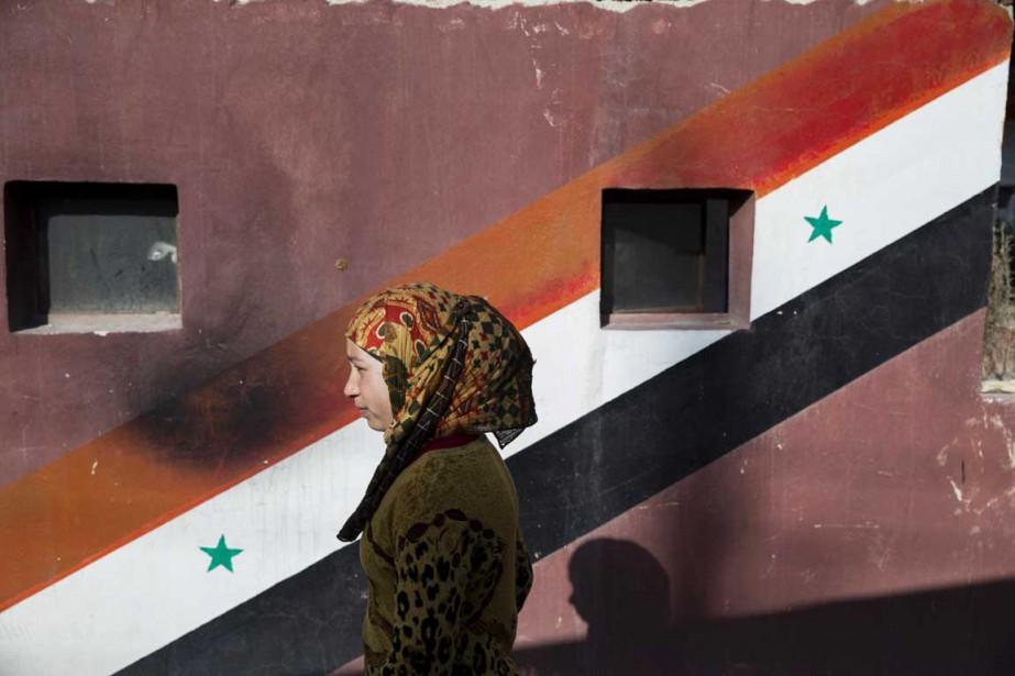 Une femme passe devant un drapeau syrien peint... (PHOTO PAVEL GOLOVKIN, AP)