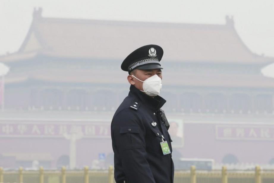 Un policier porte un masque pour se protéger... (PHOTO KIM KYUNG-HOON, REUTERS)