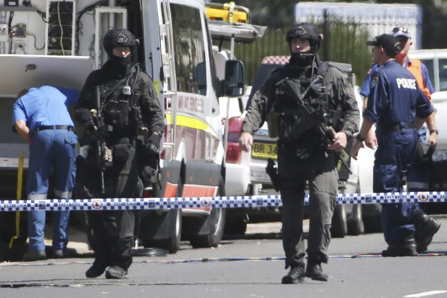 Des policiers lourdement armés encerclaient l'édifice situé dans... (Photo Rick Rycroft, AP)