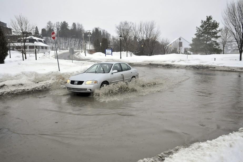 La pluie a commencé en fin d'après-midi. En raison des accumulations de neige en bordure des chaussées, l'eau ne s'évacuait pas adéquatement. (Photo Le Quotidien, Rocket Lavoie)