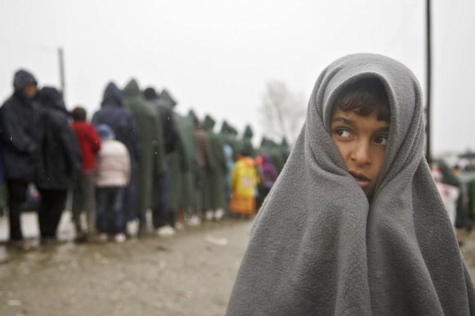 Un enfant se protège de la pluie tant... (PHOTO VISAR KRYEZIU, AP)