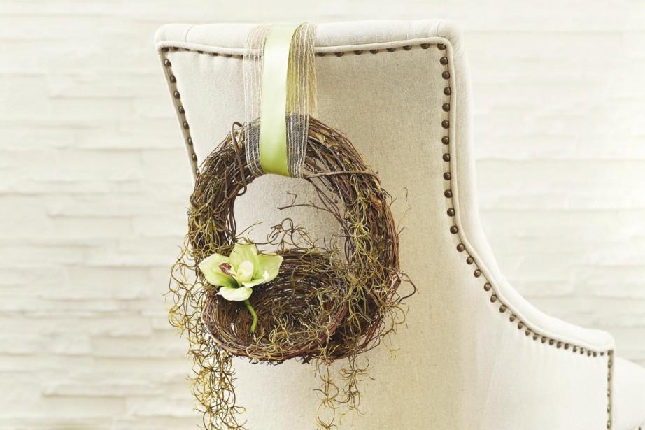 On peut garnir le dossier des chaises de couronnes de vignes, de nids, d'un peu de verdure et de mousse espagnole, le tout retenu par un joli ruban, pour créer une décoration organique et douce. (Photo fournie par Michael's)