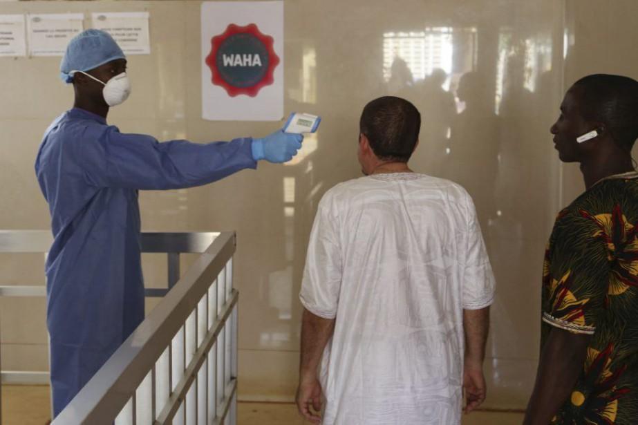 Un travailleur de la santé prend la température... (Photo Youssouf Bah, Associated Press)
