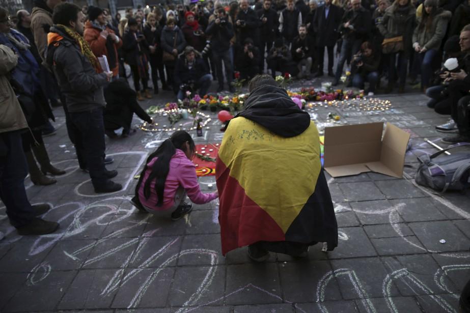 Les gens ont été nombreux à se rendre à la place de la Bourse, devenu le lieu de recueillement des Bruxellois, pour y déposer des fleurs et des bougies. (AFP, Kenzo Tribouillard)