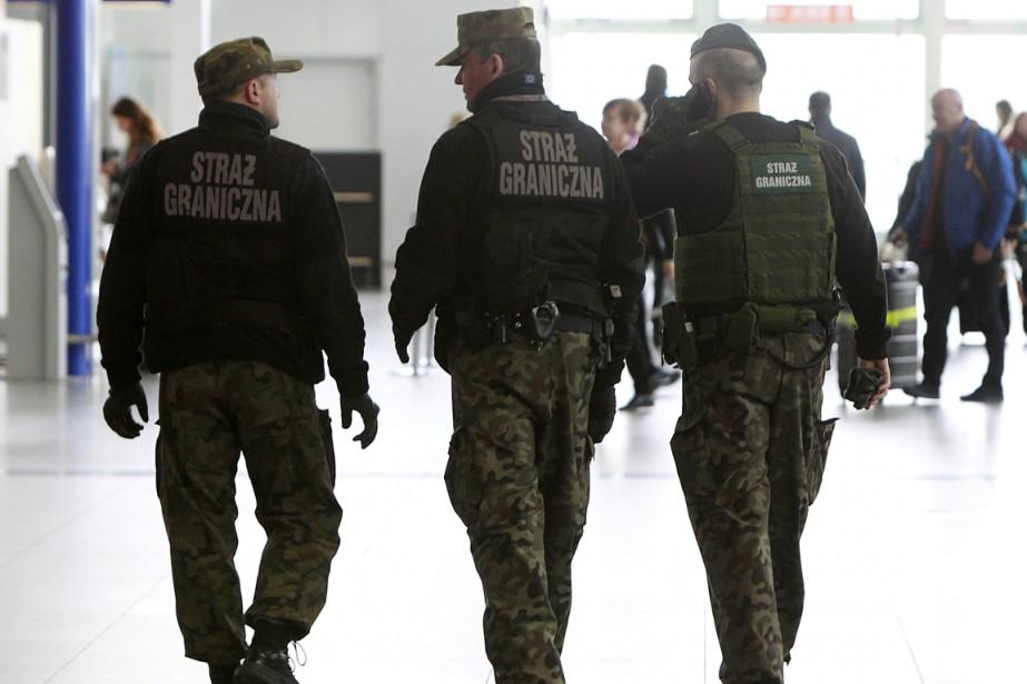 Des policiers patrouillent dans un aéroport de Varsovie.... (Photo AP)