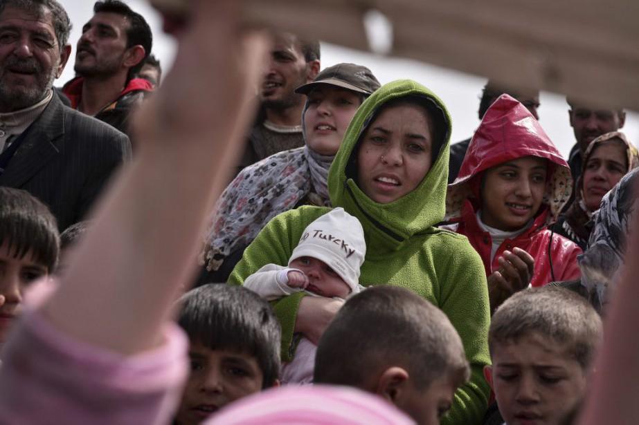 Des réfugiés au port de Chios.... (PHOTO LOUISA GOULIAMAKI, AGENCE FRANCE-PRESSE)