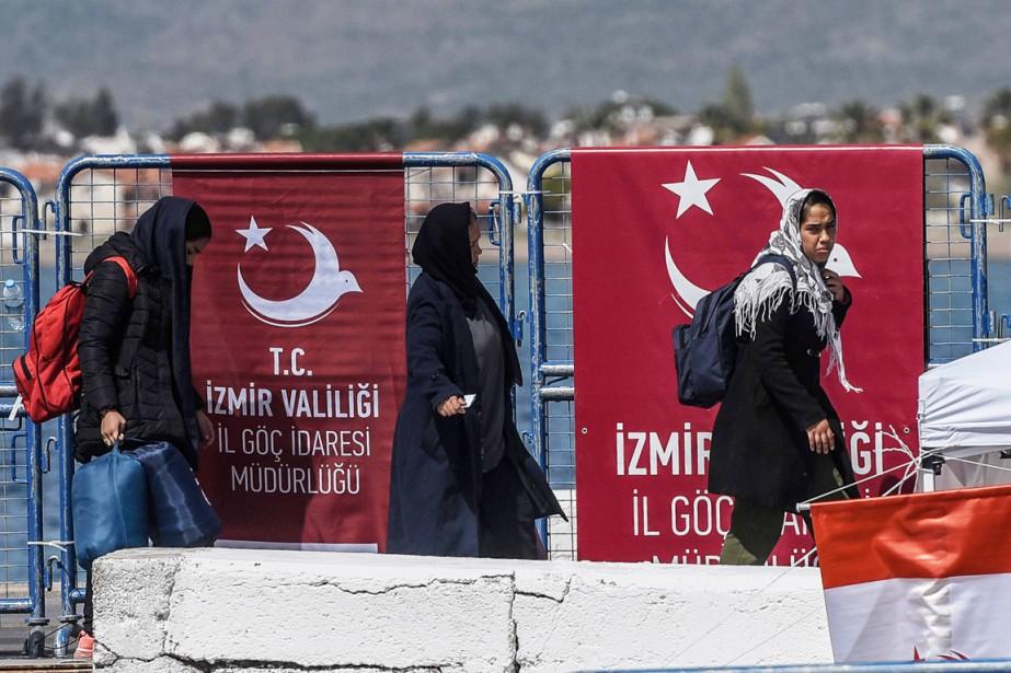 Des femmes descendent d'un traversier turc transportant les... (PHOTO OZAN KOSE, AFP)