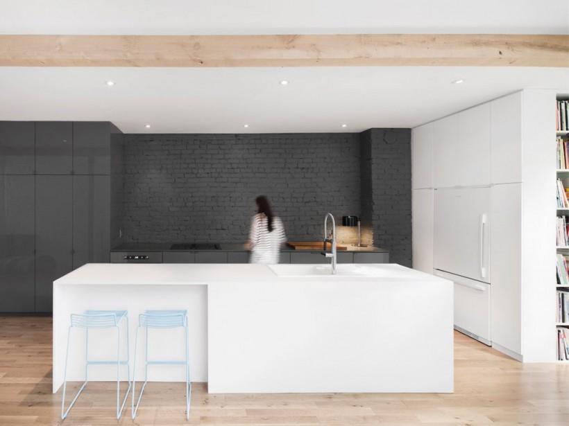 Dans la cuisine de ce projet baptisé Espace Panet, l'îlot de près de 12 pieds de long est enveloppé de stratifié blanc mat. Et c'est par la couleur qu'une zone a été adroitement délimitée: une peinture gris anthracite au fini mat a été appliquée sur la brique d'origine du mur mitoyen. Aussi, celle-ci s'inscrit dans la continuité des armoires également grises, mais présentant un fini lustré. (PHOTO ADRIEN WILLIAMS, FOURNIE PAR ANNE SOPHIE GONEAU DESIGN)