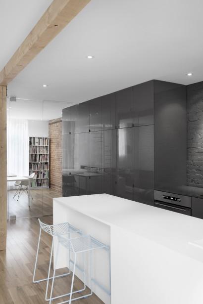 Derrière la première porte du long rangement, au premier plan, se cache un garde-manger. Ensuite, on trouve un vaisselier, suivi d'une armoire regroupant de petits électroménagers et d'une penderie, pour l'entrée. Une paroi de verre trempé vient se glisser dans le «mur» d'armoires afin de délimiter le bureau, sans séparer l'espace. Les deux dernières armoires servent de rangement pour le lieu de travail. Celui-ci peut se transformer en chambre. (PHOTO ADRIEN WILLIAMS, FOURNIE PAR ANNE SOPHIE GONEAU DESIGN)