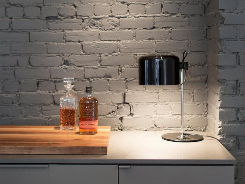 Une lampe de table (celle-ci a été dessinée par le célèbre designer italien Joe Colombo) posée près d'une carafe à spiritueux de style <em>vintage</em> insuffle une note décontractée à une cuisine épurée. La planche à découper est en noyer, le comptoir, en quartz gris et la vieille brique a été couverte d'une peinture mate. Remarquez la variété des finis et la richesse des textures. (PHOTO ADRIEN WILLIAMS, FOURNIE PAR ANNE SOPHIE GONEAU DESIGN)