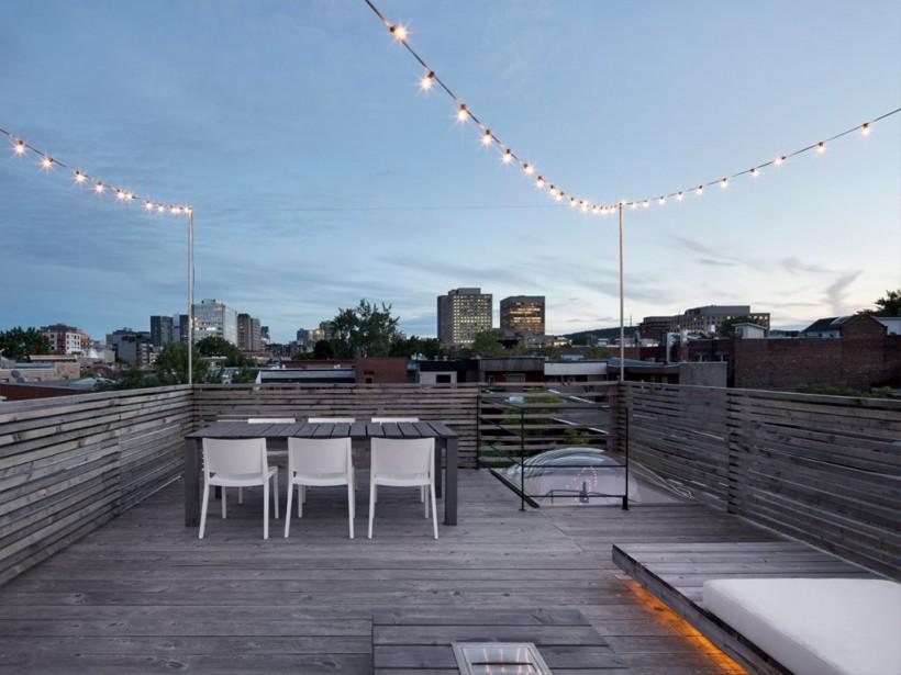 Il est possible d'accéder à la terrasse sur le toit grâce à un puits de lumière ouvrant, qui coiffe un escalier en colimaçon. Les garde-corps ajourés et le sol sont faits de pruche. Remarquez:l'espace entre les planches du garde-corps, à proximité du puits, a été augmenté afin de mieux laisser passer la lumière. (PHOTO ADRIEN WILLIAMS, FOURNIE PAR ANNE SOPHIE GONEAU DESIGN)