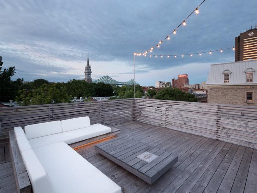 Situé au dernier étage d'un triplex de l'arrondissement de Ville-Marie, près du pont Jacques-Cartier, à Montréal, cet appartement avec toit-terrasse offre une vue magnifique sur la ville. La banquette en angle, dont la base est rehaussée d'un fil de lumière, ainsi que la table basse avec foyer à l'éthanol intégré ont été confectionnées avec du cèdre blanc. (PHOTO ADRIEN WILLIAMS, FOURNIE PAR ANNE SOPHIE GONEAU DESIGN)