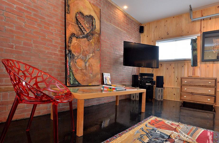 Une salle de télévision a été aménagée dans le garage. Le propriétaire lui a ajouté un mur de fausses briques. (Le Soleil, Patrice Laroche)