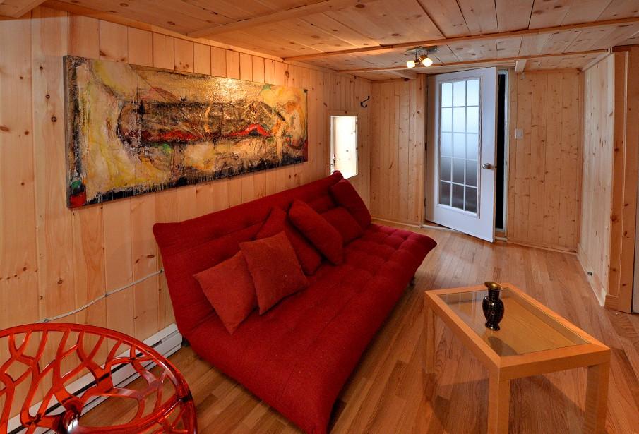 Jean Gaudreau a «levé» la maison afin de la doter d'un sous-sol qui lui sert de salon. Il a signé l'oeuvre au-dessus du canapé. (Le Soleil, Patrice Laroche)