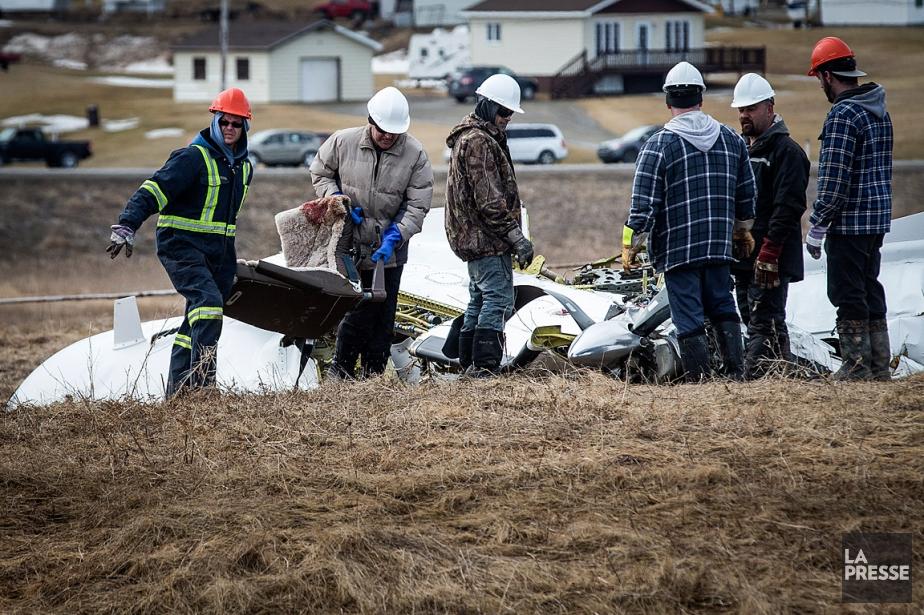 Des ouvriers démantèlent l'avion qui s'est écrasé aux... (PHOTO OLIVIER PONTBRIAND, LA PRESSE)