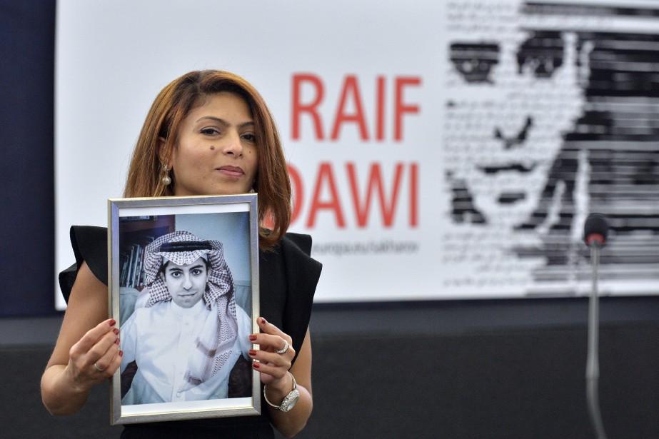 Ensaf Haidar tient un portrait de son époux... (PHOTO PATRICK HERTZOG, ARCHIVES AGENCE FRANCE-PRESSE)