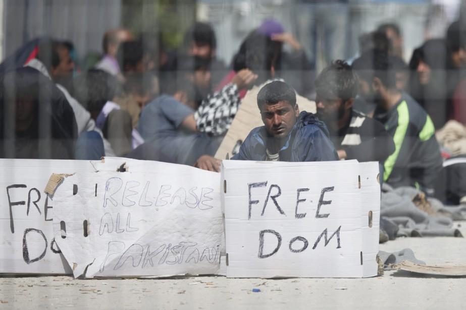Vus à travers une clôture grillagée, des migrants... (PHOTO PETROS GIANNAKOURIS, AP)