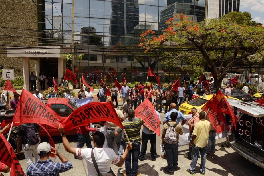 Des dizaines de personnes ont manifesté en bas... (PHOTO ED GRIMALDO, AFP)