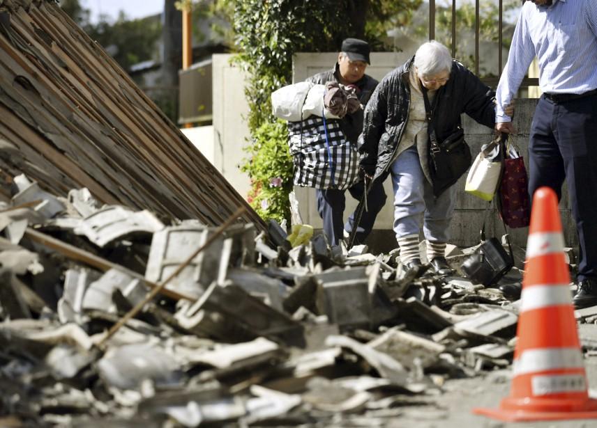 Des résidents de la ville de Mashiki, dans la préfecture de Kumamoto, évacuent leur maison endommagée par les séismes. (Yu Nakajima, Kyodo News via AP)