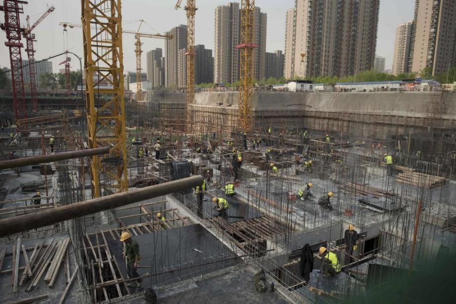 Des ouvriers travaillent sur un site de construction... (PHOTO NICOLAS ASFOURI, AFP)
