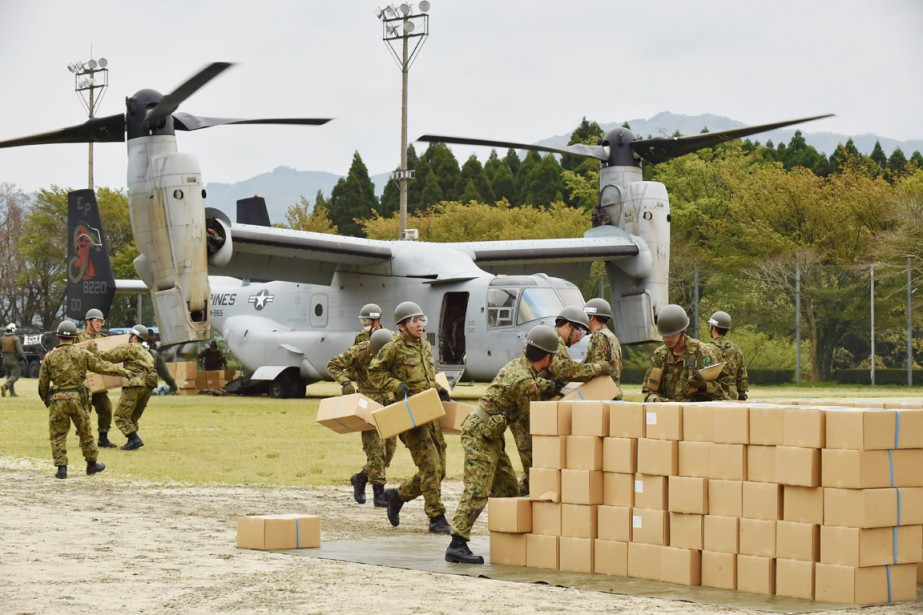 Des membres des forces d'autodéfense déchargent des cartons... (PHOTO KAZUHIRO NOGI, AFP)