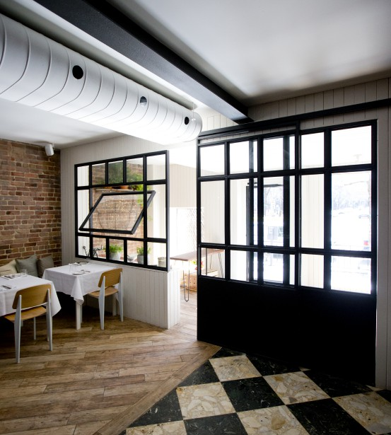 Verrière d'atelier : en acier noir, cette nouvelle cloison vitrée du restaurant Chambre à part évoque les anciennes verrières d'atelier françaises. Elle comporte une porte coulissante, une fenêtre basculante et délimite le hall d'entrée. «Cette cloison permet de souligner la zone de transition entre l'extérieur et l'ambiance du restaurant», explique la copropriétaire Stéphanie Labelle, qui a conçu l'aménagement du lieu avec la collaboration d'optima design. (PHOTO MARCO CAMPANOZZI, LA PRESSE)