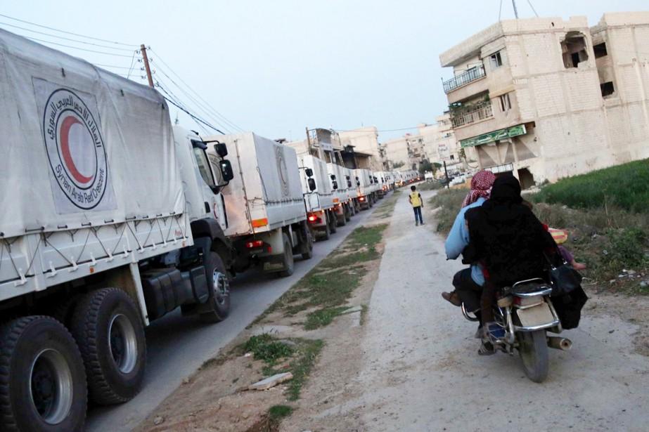 Une famille roulant à scooter suit un convoi... (PHOTO AMER ALMOHIBANY, ARCHIVES AFP)