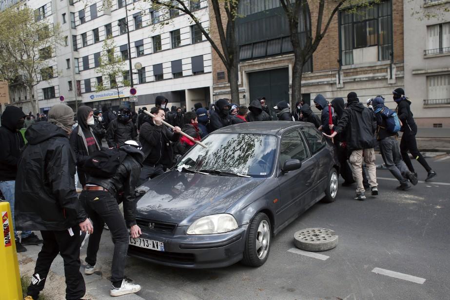 Des manifestants ont endommagé une voiture à Paris. (AP, Thibault Camus)