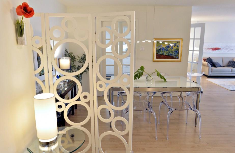 Un paravent ajouré sépare l'entrée de la salle à manger. Achetées chez Roche-Bobois, les chaises Ava allègent et animent l'espace restreint. (Le Soleil, Pascal Ratthé)