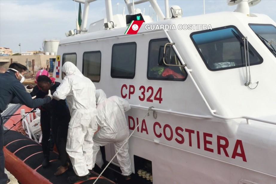 Des migrants arrivent au port de l'île de... (Photo des gardes-côte italiens via AFP)