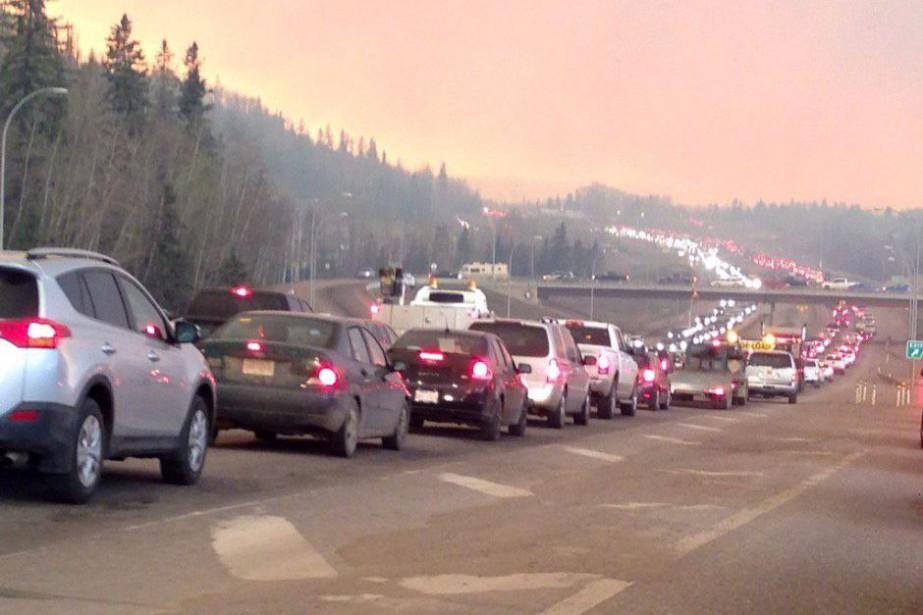 Sur cette photo provenant d'une station de radio locale, la fumée assombrit le ciel alors que des centaines de voiture font la file à Fort McMurray, où la moitié de la ville fait l'objet d'une ordonnance d'évacuation. (PC)