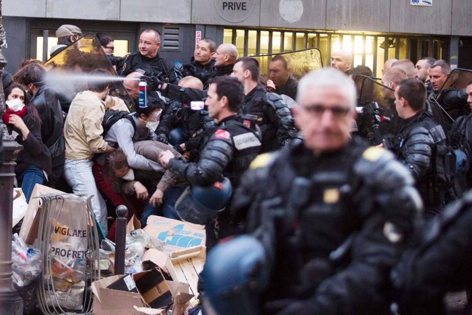 Un policier antiémeute asperge de gaz poivre un... (PHOTO GEOFFROY VAN DER HASSELT, AFP)
