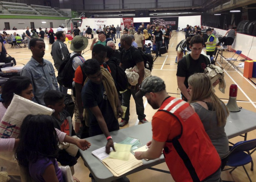 Des évacués font la queue pour s'enregistrer dans un centre d'aide d'urgence à Anzac. (PHOTO MIKE ALLEN, PC)