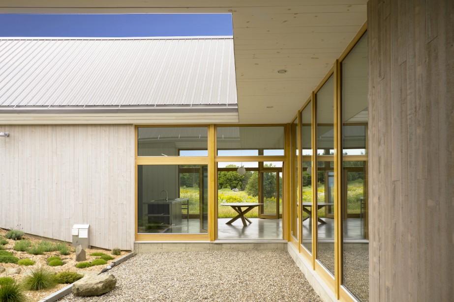 Dans la cour intérieure, rien n'obstrue la vue. À droite se trouve le passage vitré, alors que devant, on voit la salle à manger de la maison de campagne, qui s'ouvre généreusement de part et d'autre. Ici, le revêtement extérieur des murs est composé de planches de cèdre de l'Est, qui ont reçu un traitement favorisant le grisonnement du bois. (PHOTO PASCAL ANNAND, FOURNIE PAR YH2)
